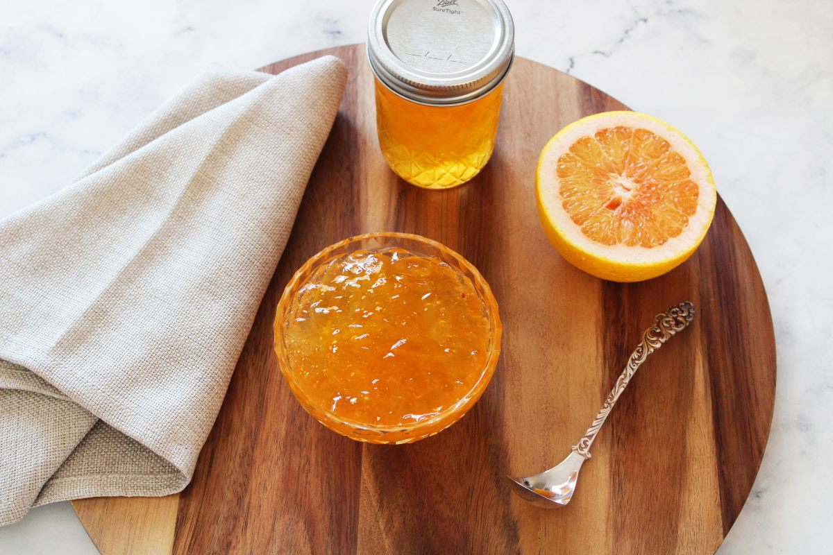 On a wooden board, bowl of marmalade, beige napkin on the left, silver spoon to the right, and behind the bowl is half a grapefruit.