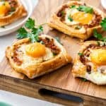 bacon and egg galettes on a wooden chopping board.