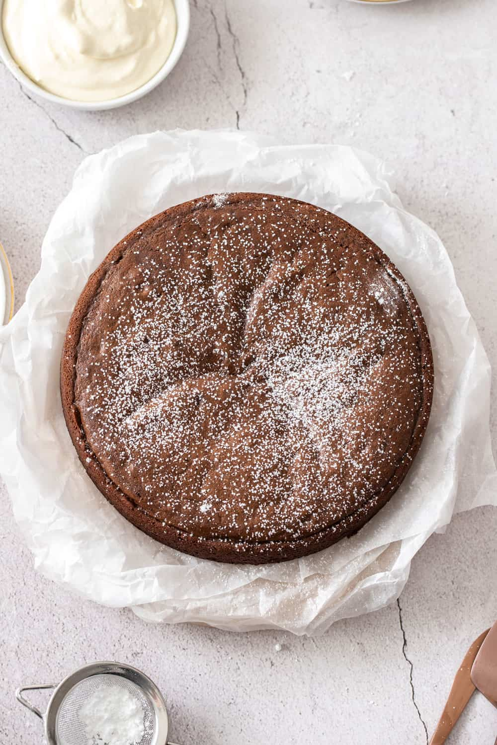 the whole cake, dusted with icing sugar, on some baking paper.