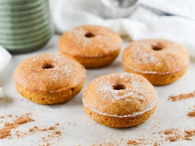 four doughnuts sitting on bench, surrounded by some sprinkling of pumpkin spice, with a white cloth and green jug in the background.