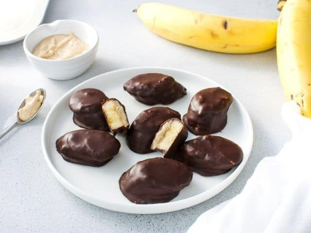 Up close shot of a plate of banana bites, some cut in half, with a bowl of peanut butter and banana, a spoon and white cloth in the background.