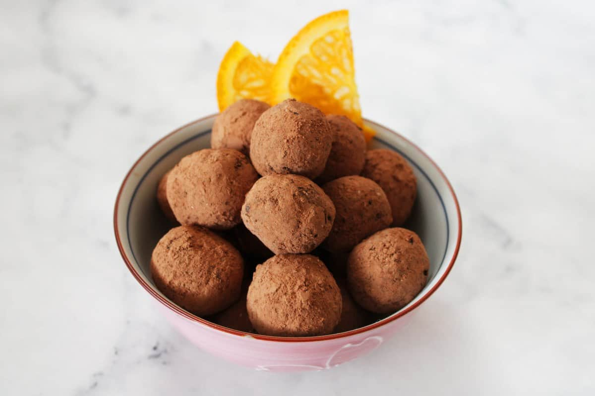 small round pink and white bowl of bliss balls, with two orange slices sitting on edge of bowl.