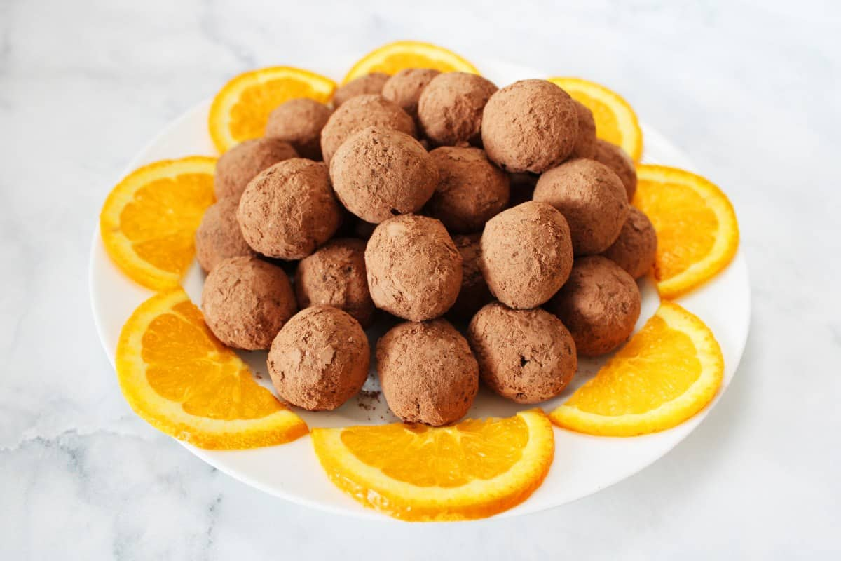 round white plate of bliss balls, surrounded by orange slices, sitting on a white marble background.