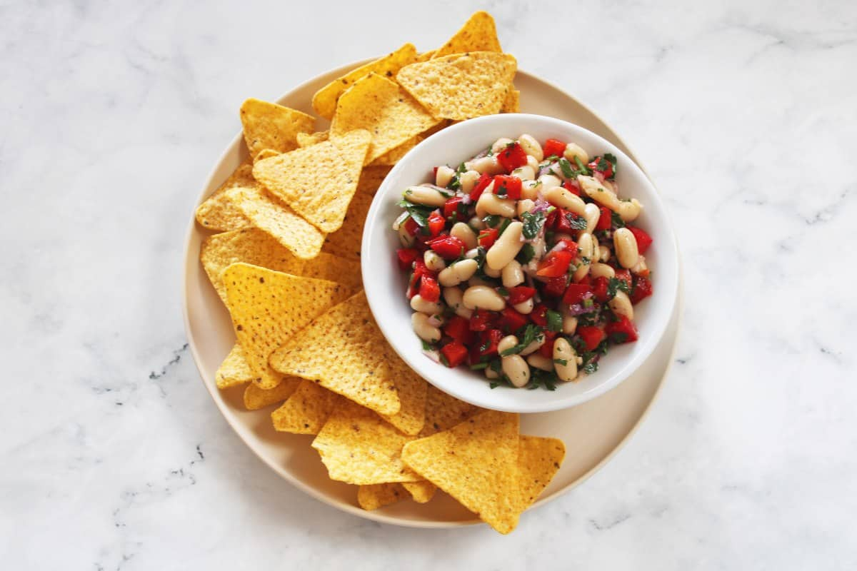 round beige plate with bowl of salsa and corn chips on a white marble background.