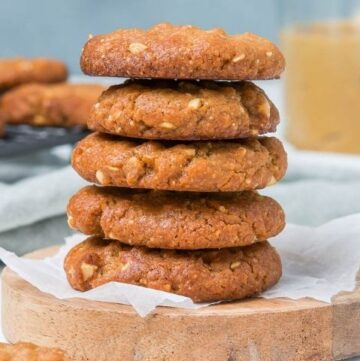 stack of cookies sitting on a round wooden board.