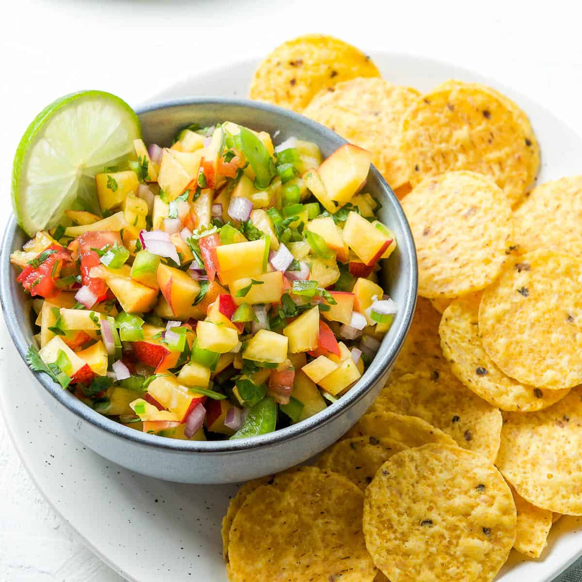 small bowl of salsa, sitting on a plate with corn chips on the side.