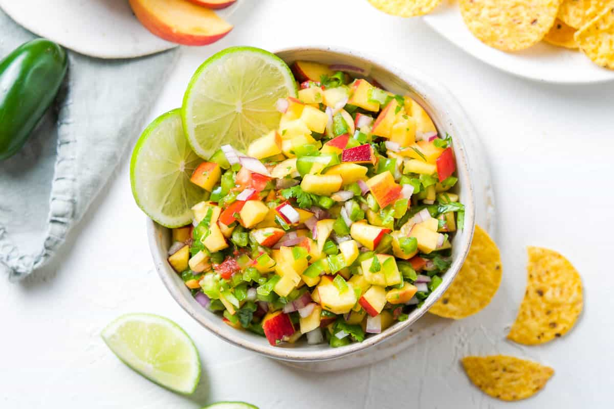 bowl of salsa, surrounded by some lime wedges, corn chips, peach slices and jalapeño.