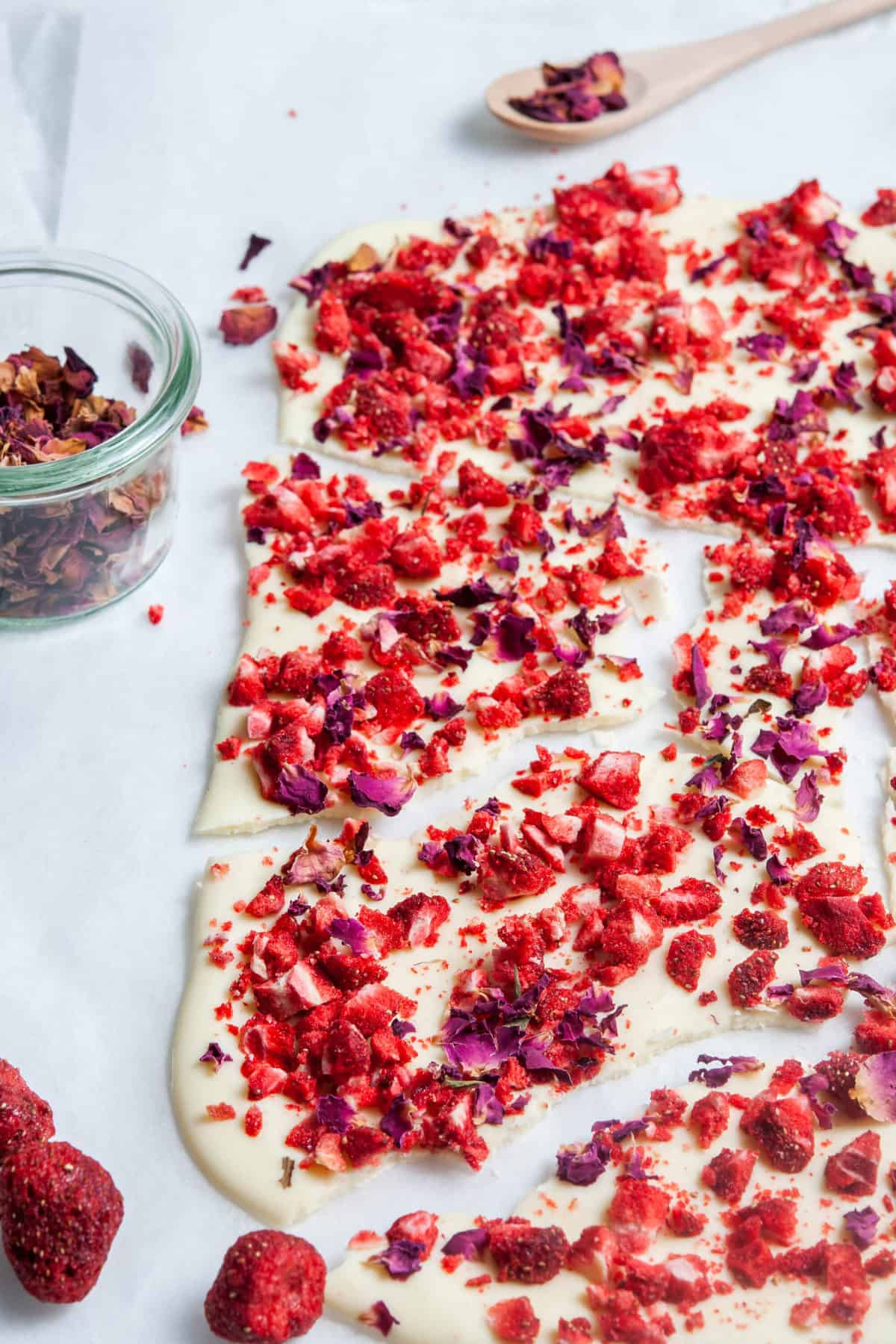 shards of chocolate bark, with some freeze dried strawberries at front, small glass dish of rose petals on side, and a small wooden spoon holding some rose petals at the back.