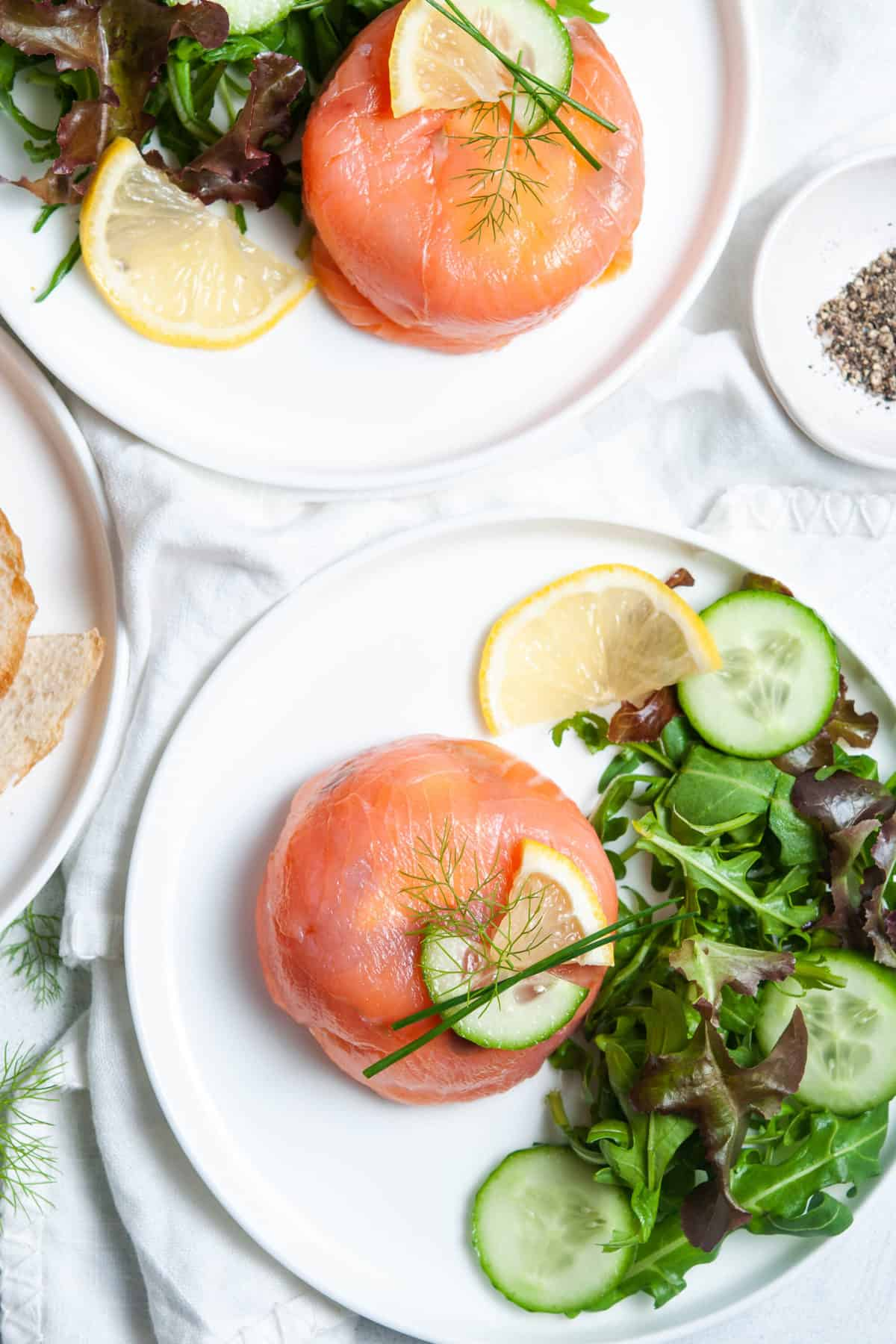 overhead shot of salmon parcel, on white plate, with salad on the side and a lemon garnish, another plate with same sitting in background.