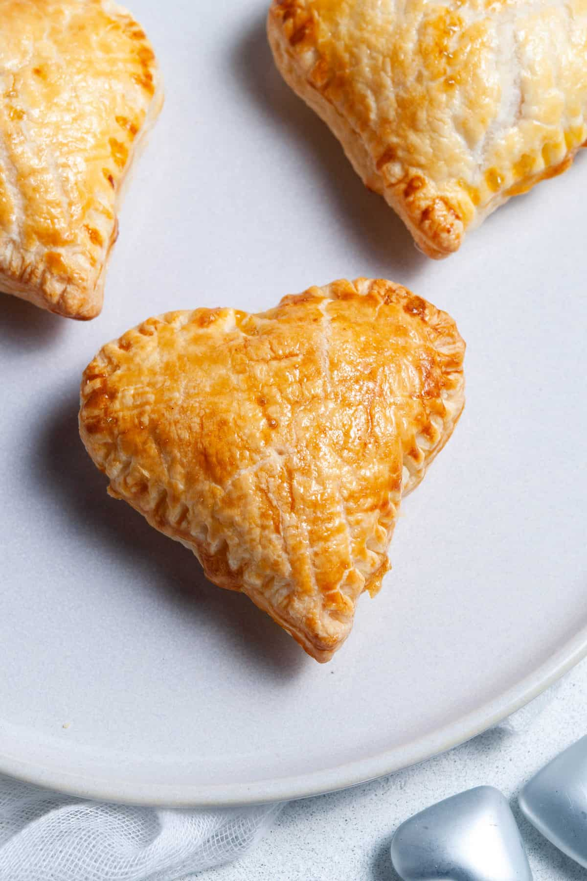 up close shot of three pastry hearts that have been cooked.