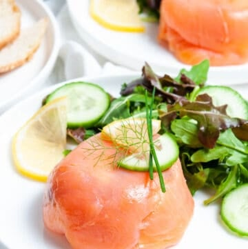 salmon parcel, on white plate, with salad on the side and a lemon garnish, another plate with same sitting in background.