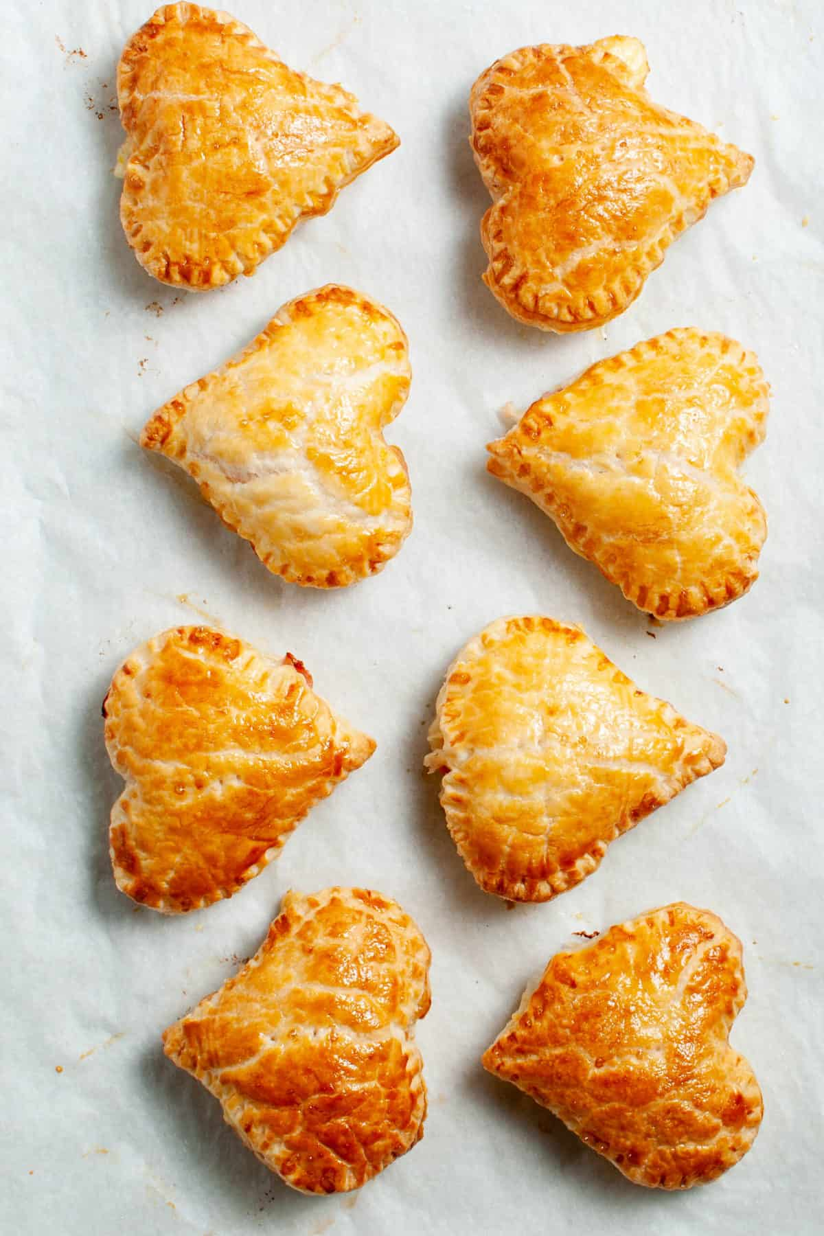 eight pastry hearts, having been baked, sitting on a piece of baking parchment.