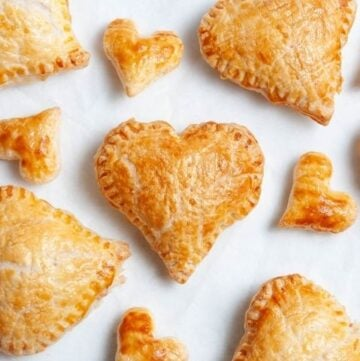 heart pastries and smaller heart pastries on a white baking sheet.