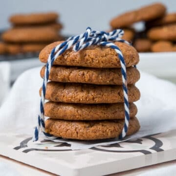 Stack of cookies, tied with a blue and white string, sitting on a white tile, with cookies in the background.