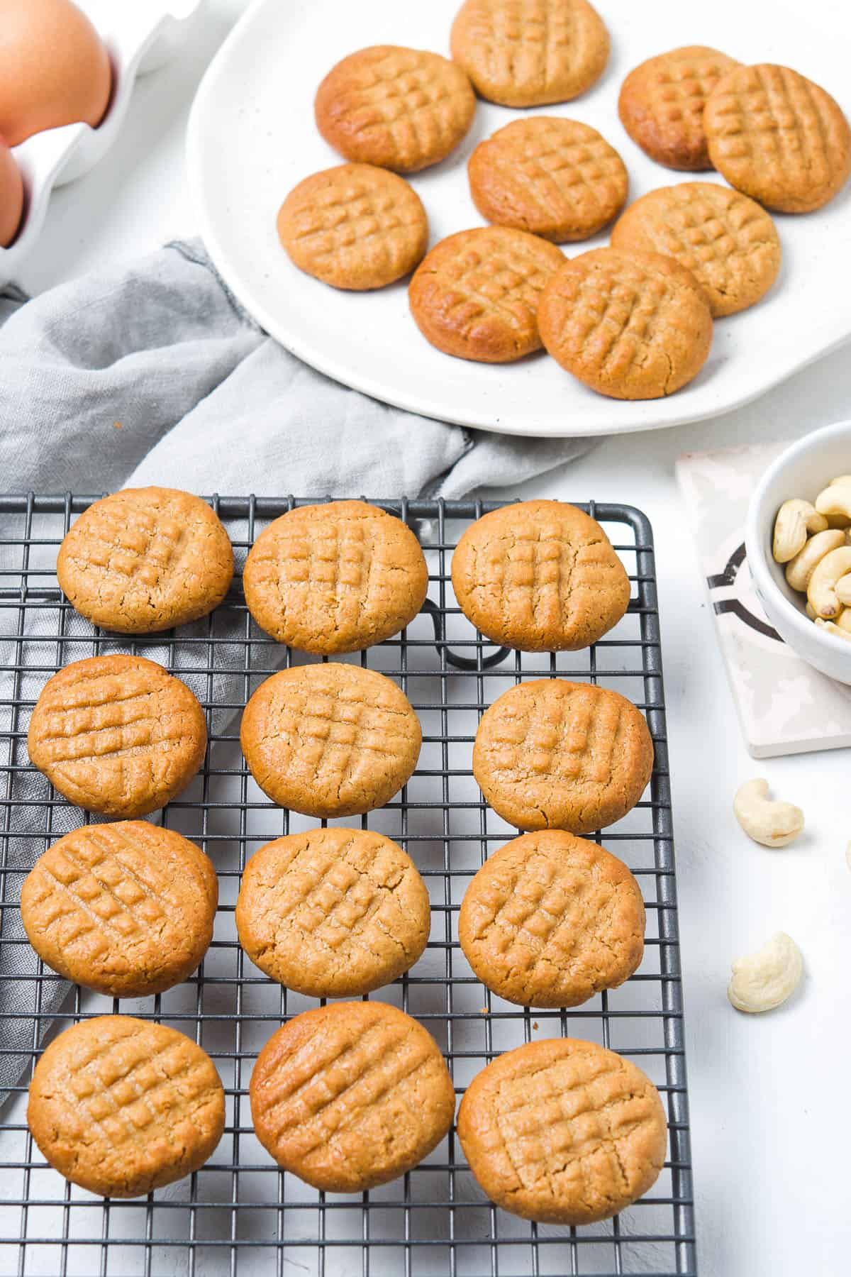 cookies on a cooling rack, with some on a plate in the background, surrounded by some cashews.