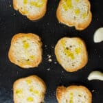 six pieces of bread, toasted on a baking tray, with some garlic cloves around the edge.