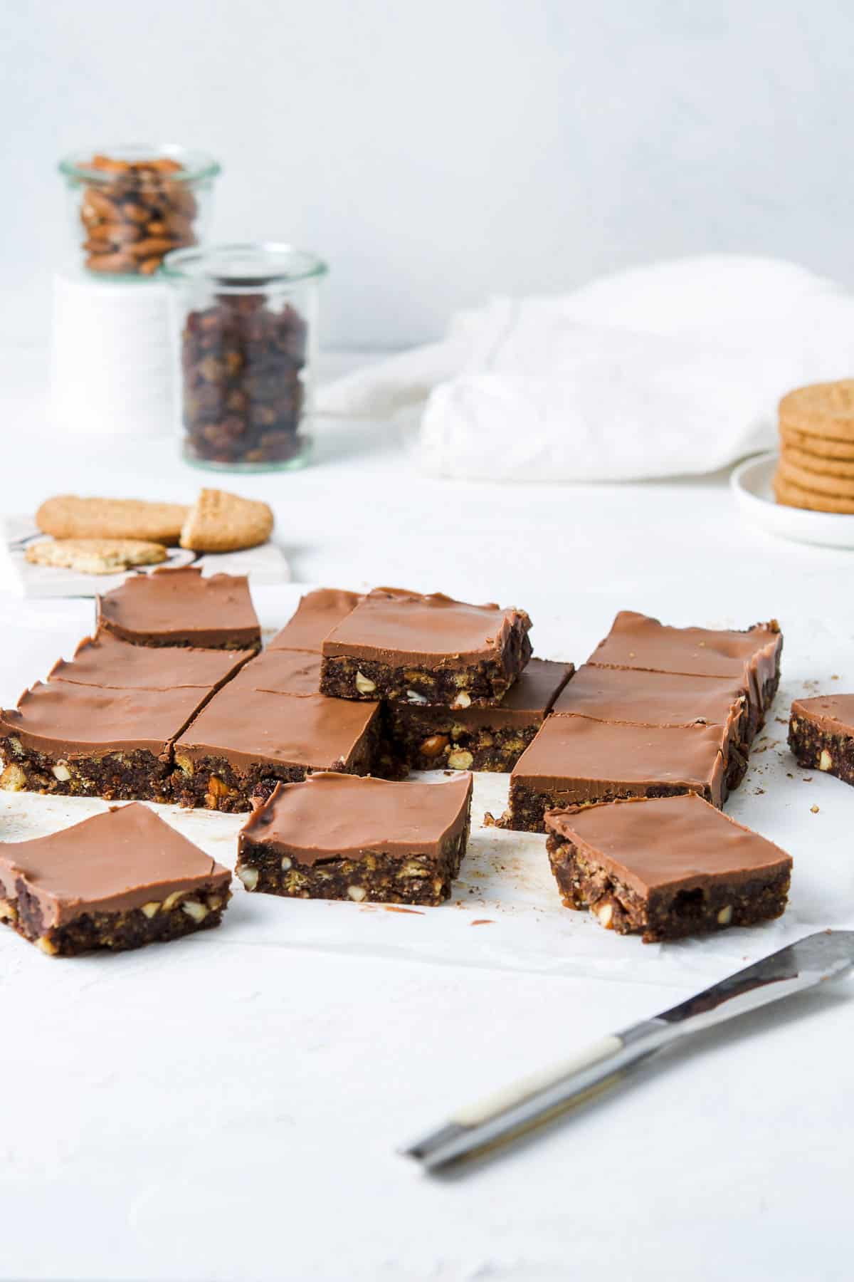slices of chocolate tiffin on a white bench, with some biscuits in the background.