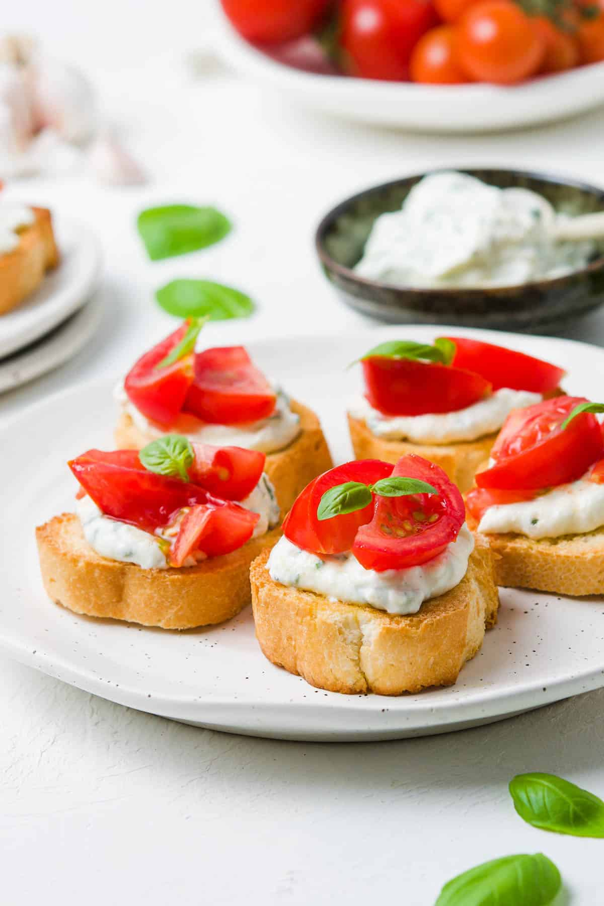 five crostini on a white plate.