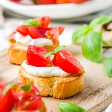 up close shot of crostini on a wooden board, with a bowl of tomatoes and some basil leaves in the background.