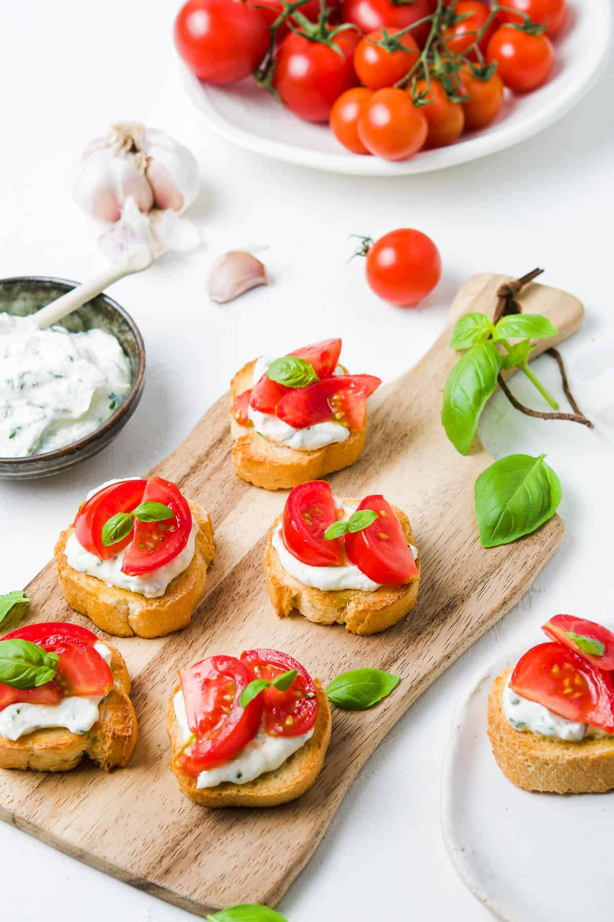 five crostini spread out on a wooden serving board, with some ricotta mixture to the side, garlic cloves and cherry tomatoes around the edge.