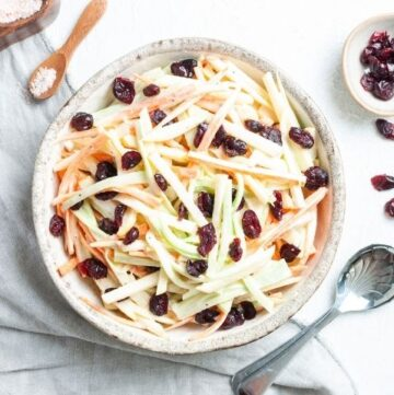 Bowl of salad on a white cloth, with some salt and pepper dishes on the edge and a dish of dried cranberries and a silver spoon on the right.