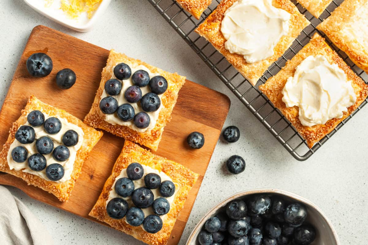 three tarts on a wooden board, with the rest on a cooling tray, and a dish of blueberries at the front.