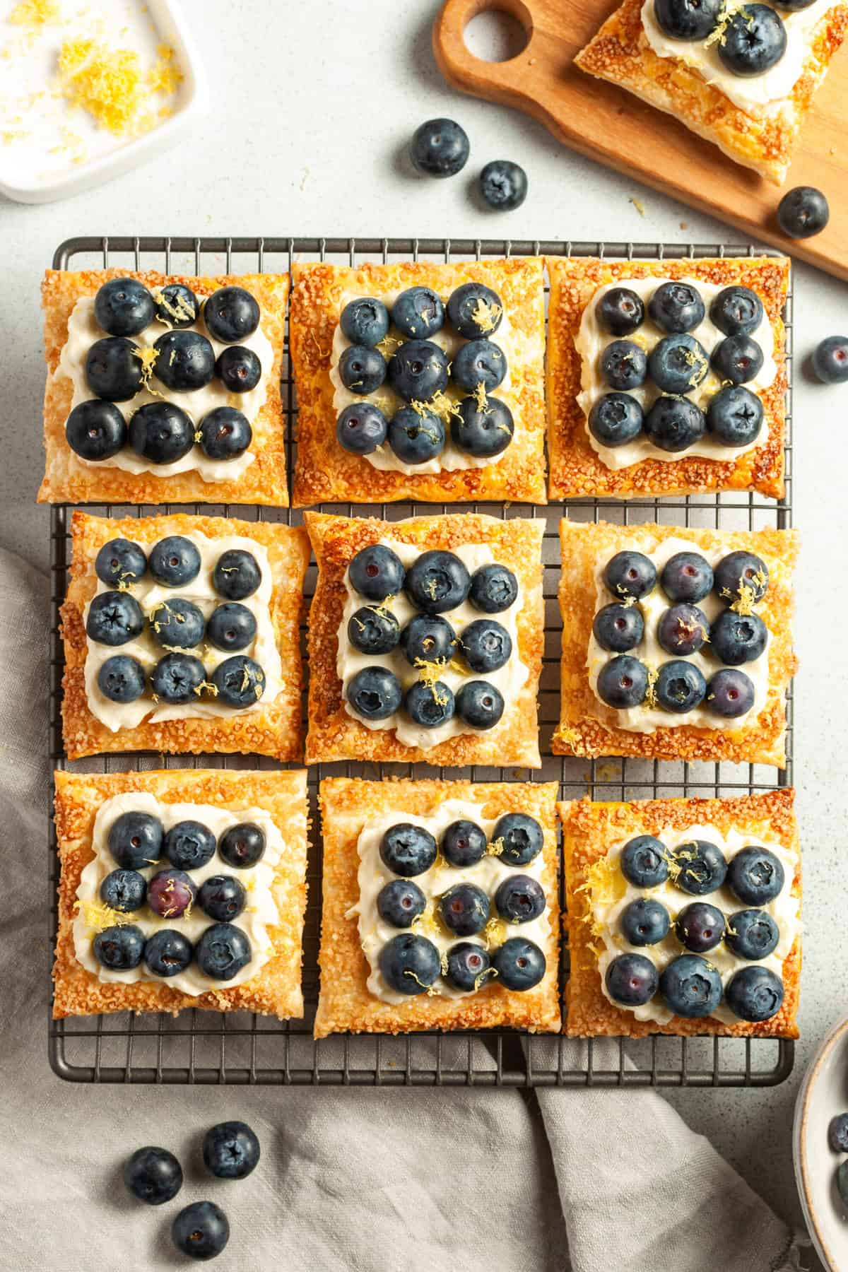 tarts sitting on a cooling rack, topped with blueberries and lemon zest.
