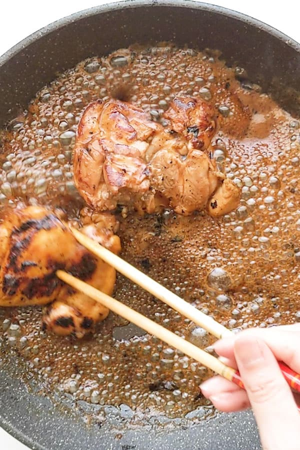 preparing teriyaki chicken using chopsticks.