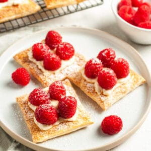 three tartlets on a round white plate, with a couple of raspberries around the edge.