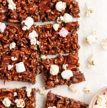overhead shot of cut popcorn bars, with some popcorn and marshmallows sprinkled around the edge.