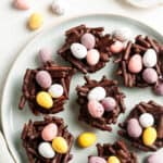 overhead shot of round white plate with easter nests filled with mini eggs, with some more mini eggs around the edge.