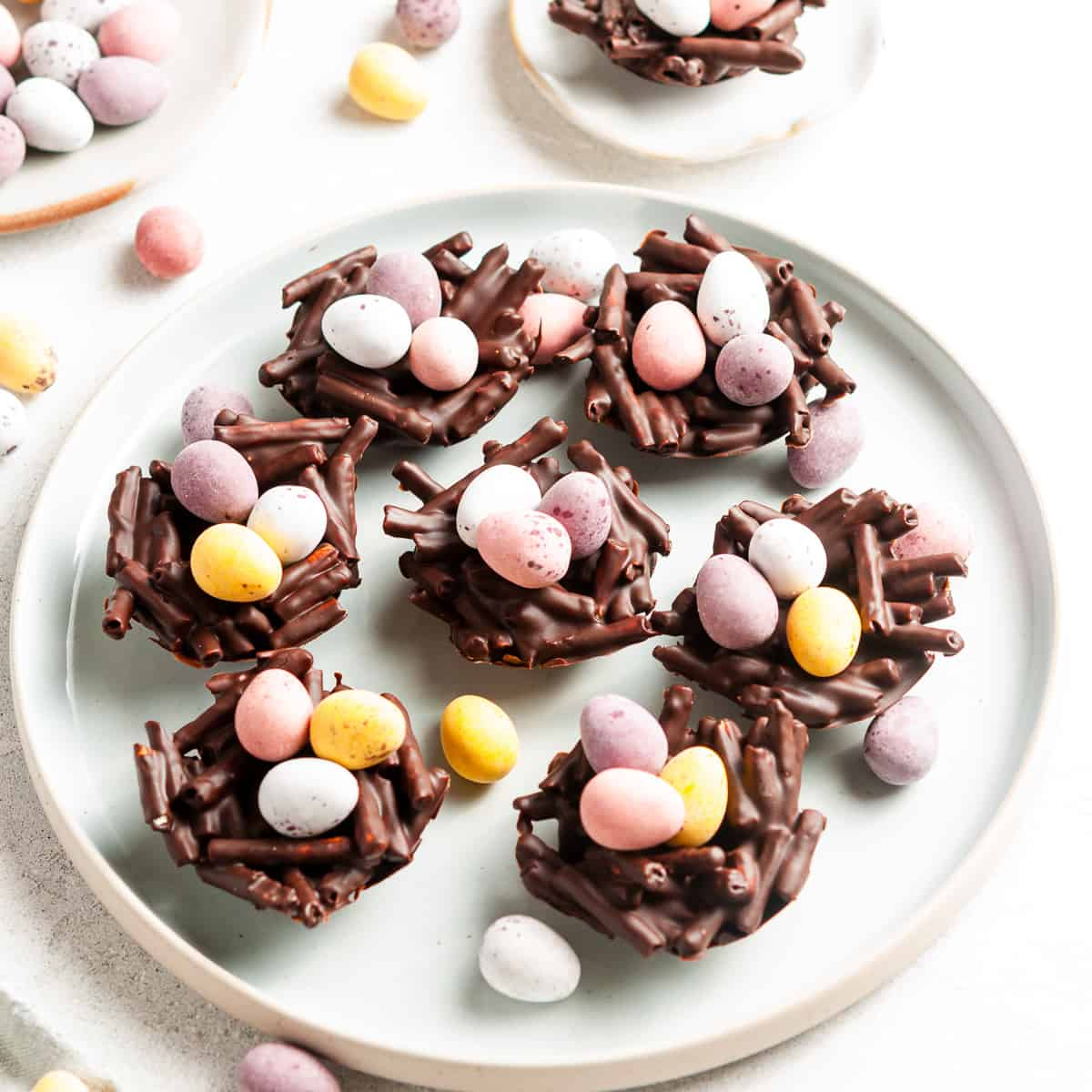 round plate of nests filled with mini eggs.