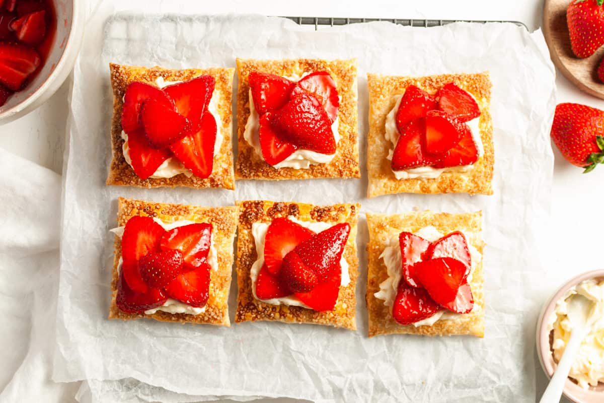 Overhead shot of 6 tartlets with some strawberries in the background and a dish of cream cheese mixture on the side.