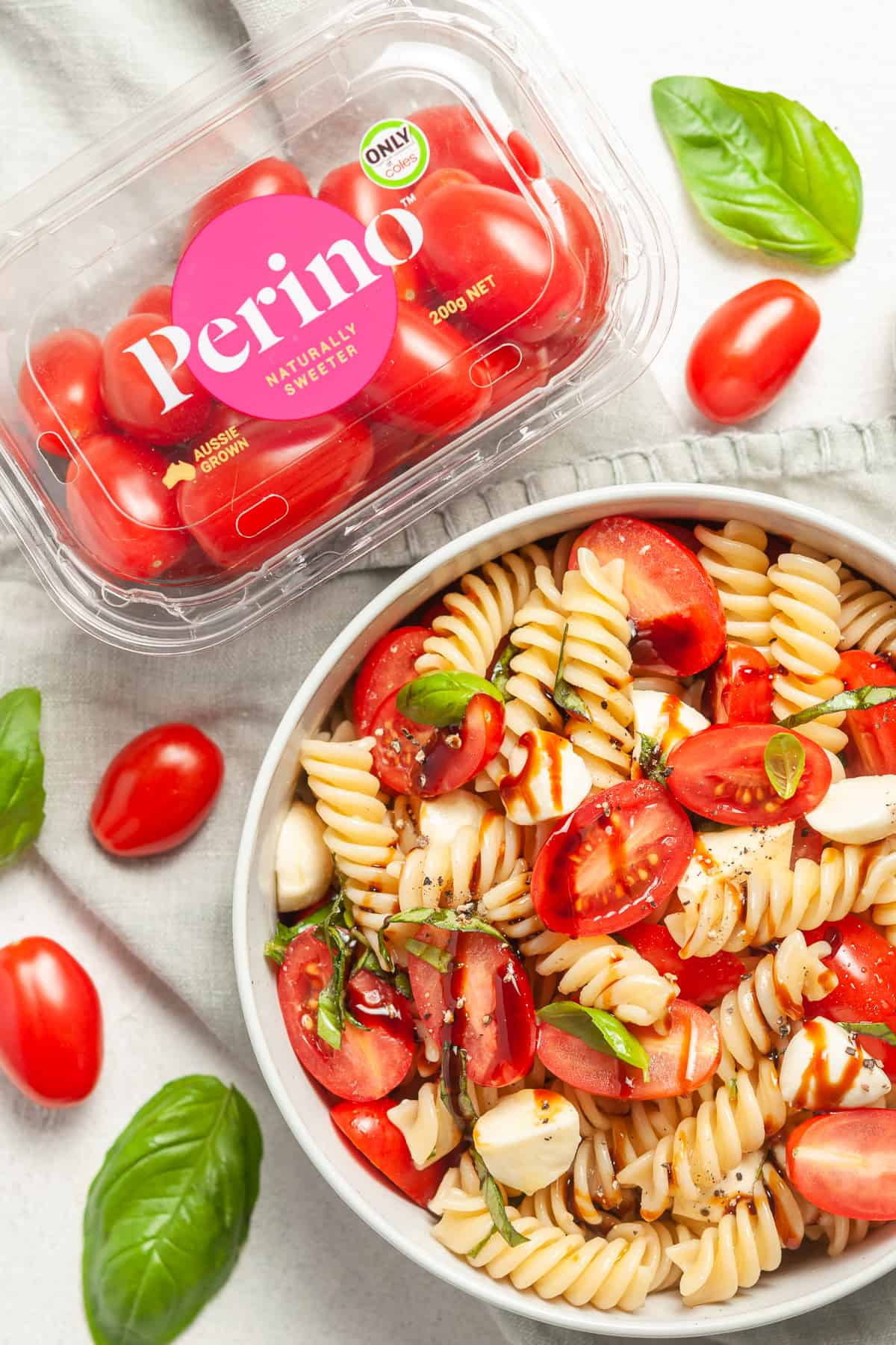 Overhead shot of pasta salad with a silver spoon on plate with a container of Perino Tomatoes and some fresh basil leaves on the side.