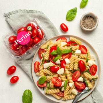 Overhead shot of pasta salad with a silver spoon on plate with a container of Perino Tomatoes on the side.
