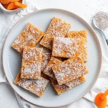 Round dish of apricot bars, with a spoon of chia seeds on the side.