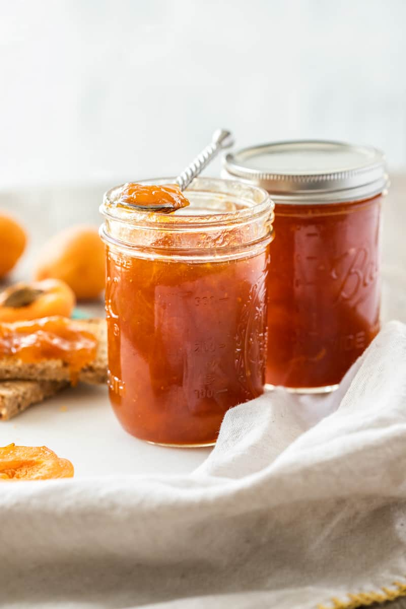Two jars of jam, one with a spoon sitting on top.