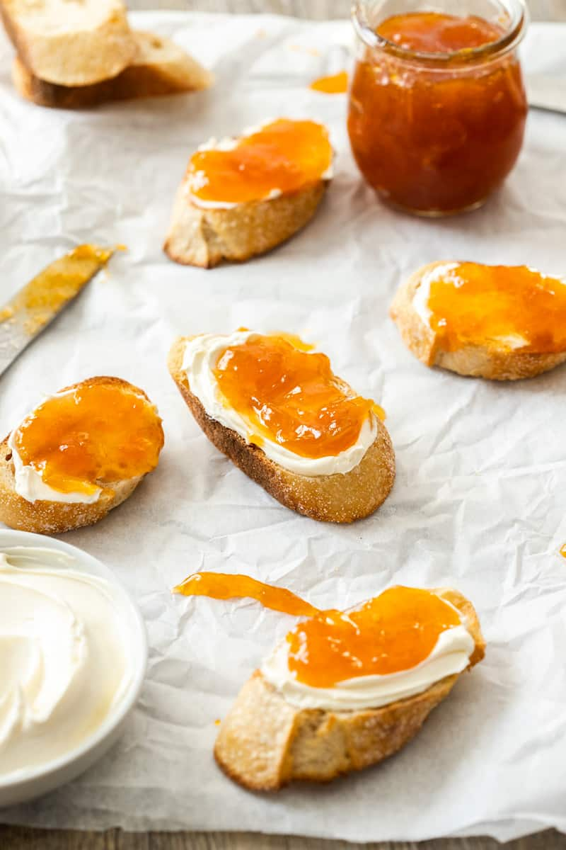 Pieces of bread topped with cream and jam, sitting on some baking paper.