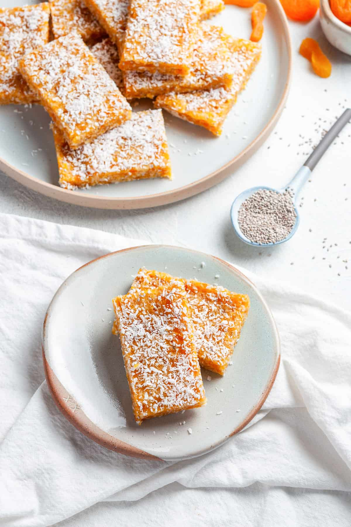 Small and large round dish of apricot bars, with a spoon of chia seeds on the side.