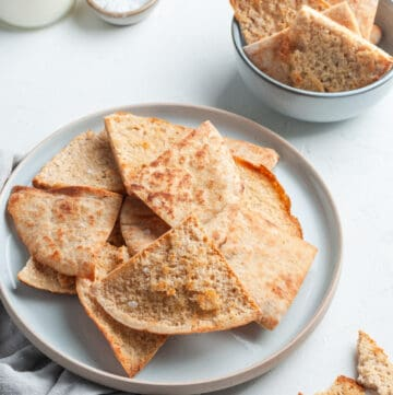 Plate of pita chips, sitting on a grey cloth.