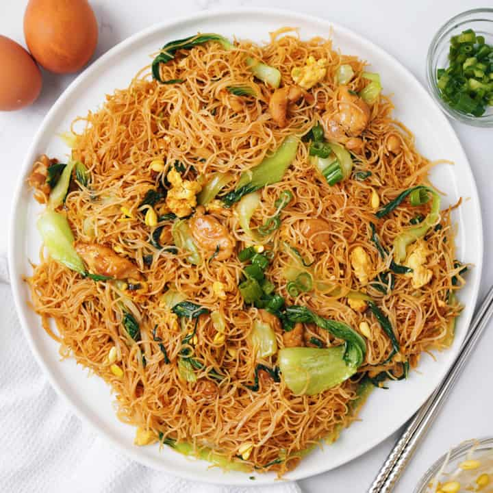 Dish of Bihun goreng noodles sitting on white cloth, with some eggs on side.