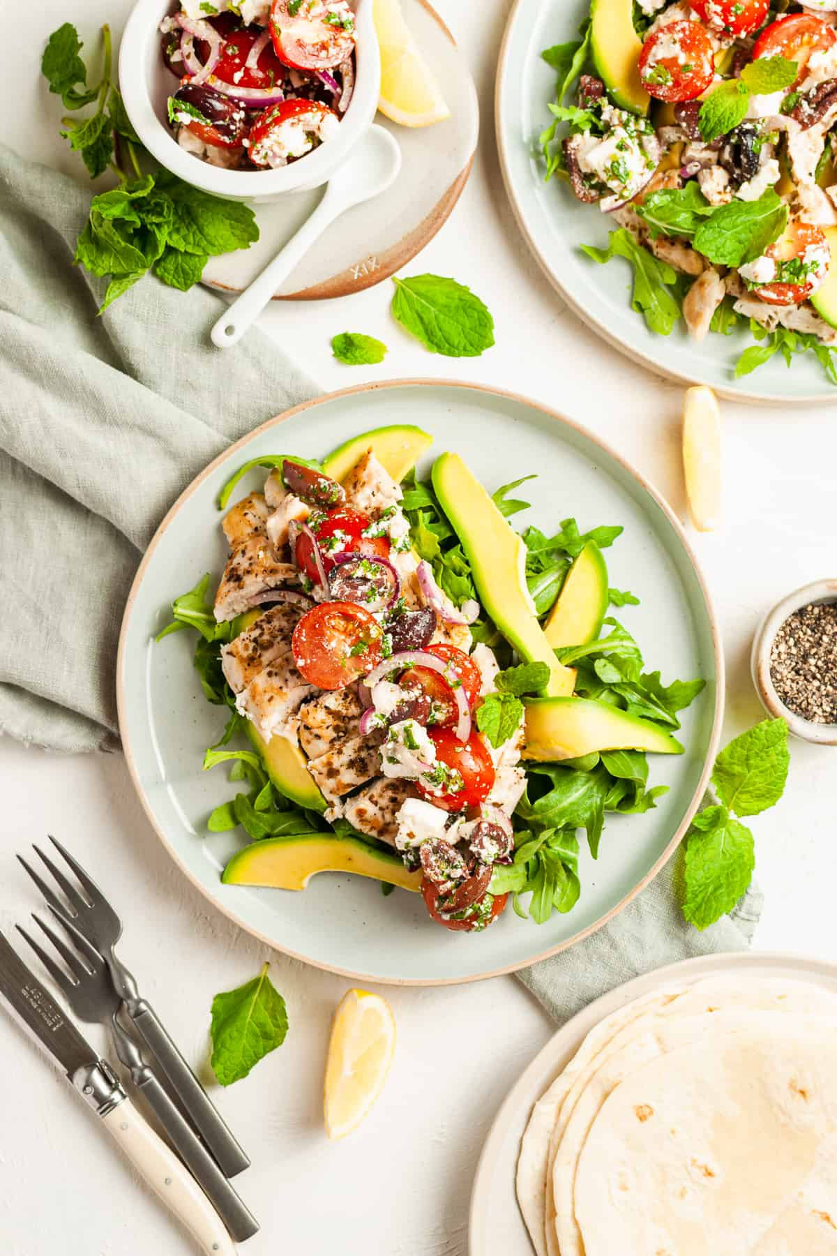 Round plate topped with salad topped with chicken and another dish of salad on the side.