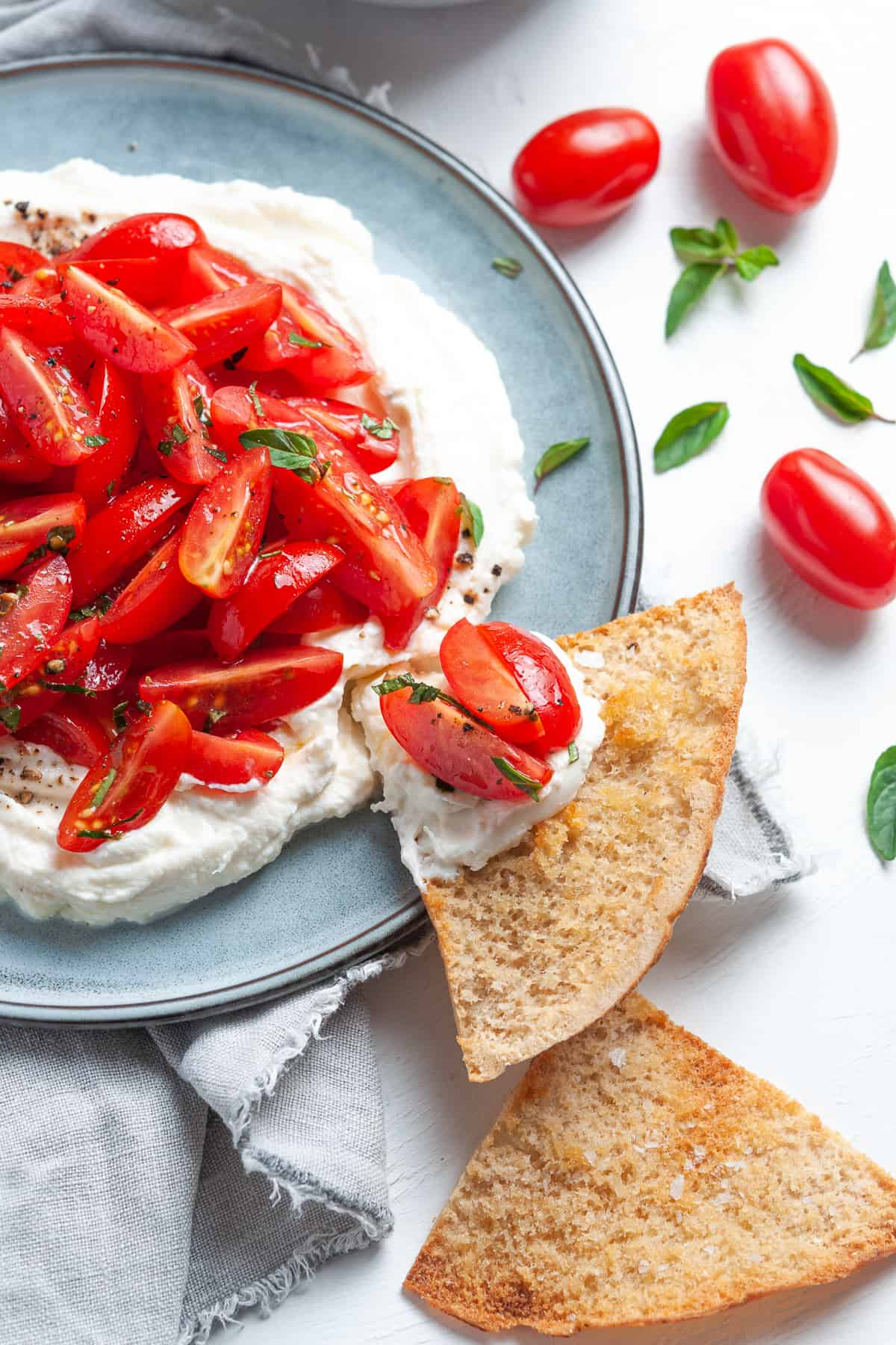 Up close shot of dish of ricotta and tomatoes, with a pita chip dipped into dish.