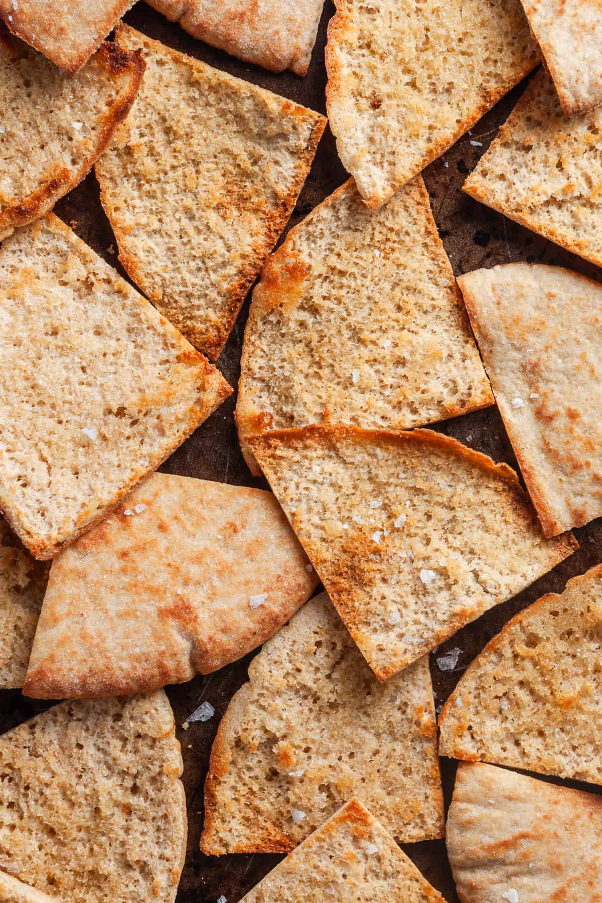 Overhead shot of cooked pita chips on a baking tray.