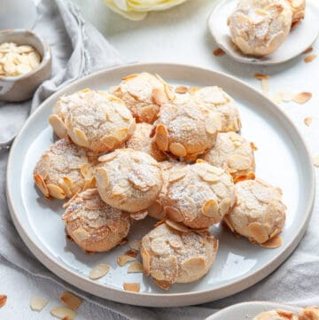 Cookies on a round white plate with some flaked almonds sprinkled around the edge.
