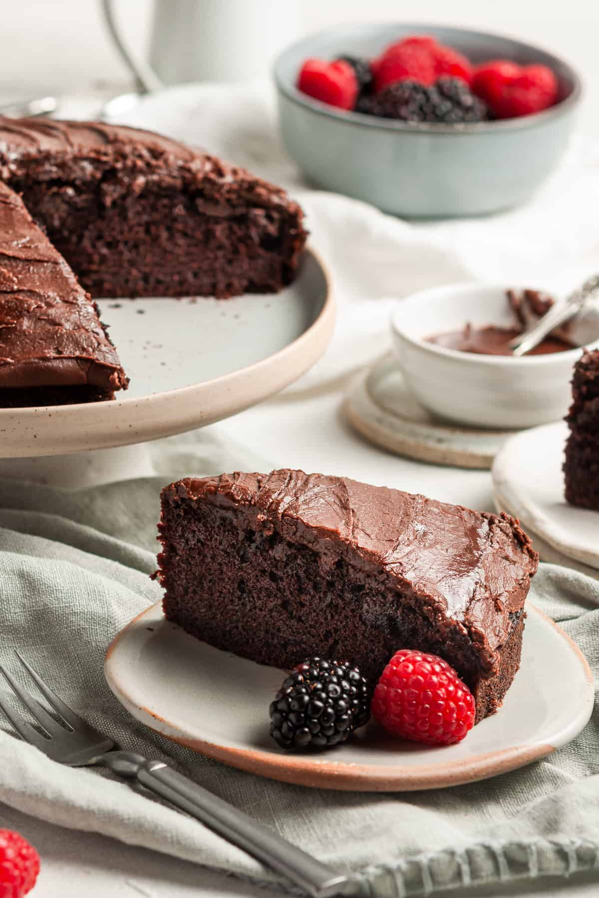 Slice of cake, sitting on a plate with some berries, with the rest of the cake in the background.