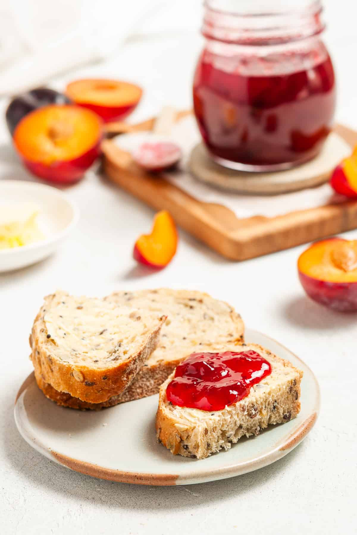 Two pieces of bread, with some jam on the top and the jar of jam and some halved plums in the background.