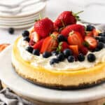 Shot of cheesecake decorated with cream and fruit.