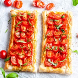 Two tomato tarts sitting on baking paper, surrounded by some tomato and basil slices.