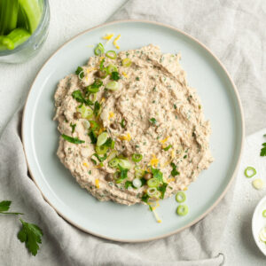 Dip served on a round blue plate, garnished with spring onions, lemon zest and capers.